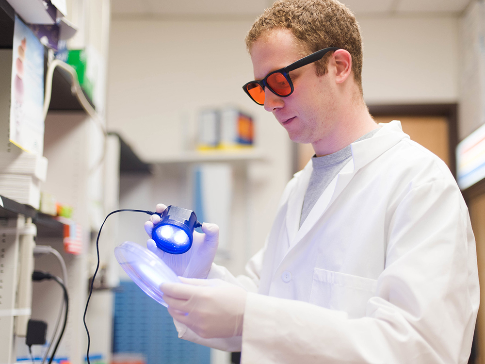 man wearing sunglasses holding electronic light in lab