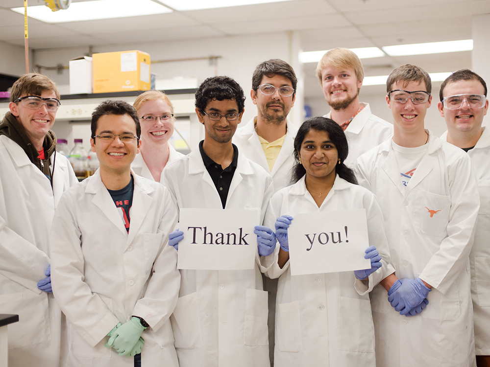 group of students in lab coats holding thank you sign